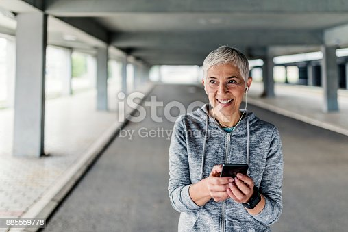 497687118istockphoto Woman with headphones preparing for a jogging 885559778