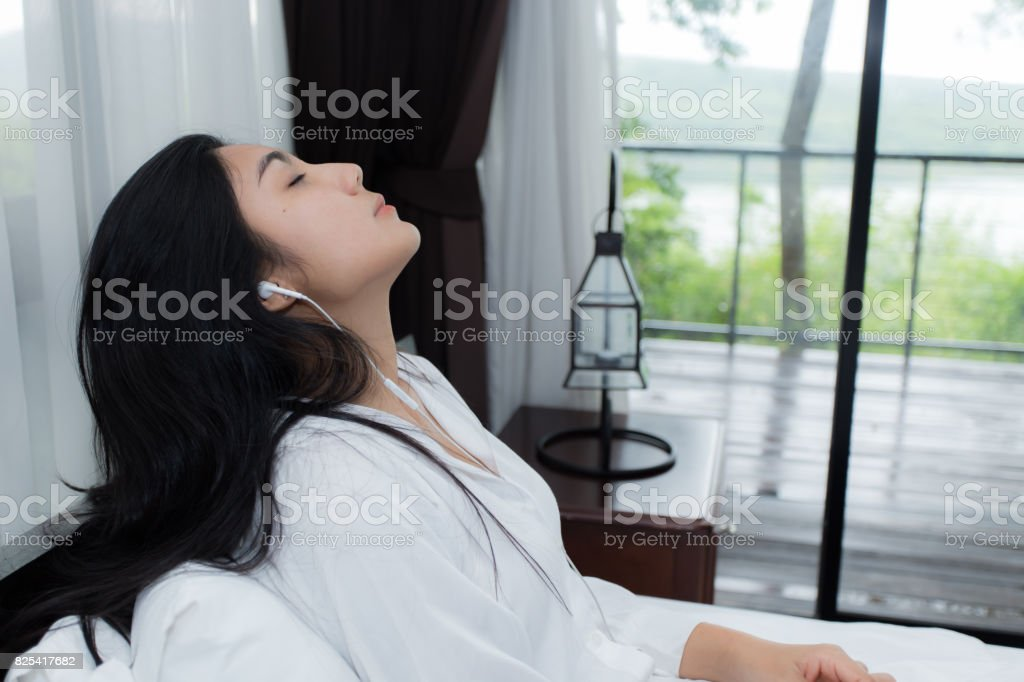 Woman with headphones relaxing on the bed stock photo