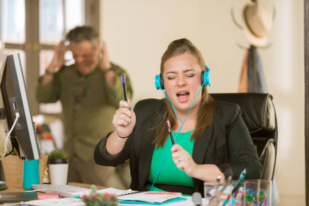 woman with headphones singing loudly and annoying colleague - rudeness stock pictures, royalty-free photos & images