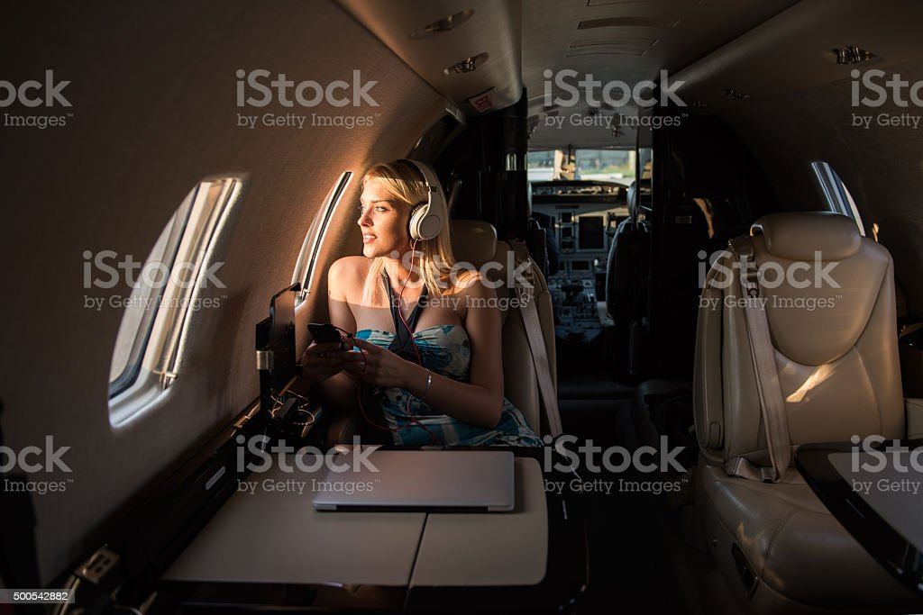 Woman with headphones sitting inside private jet airplane stock photo