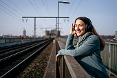istock Woman with headphones standing next to a railroad track 1308605114