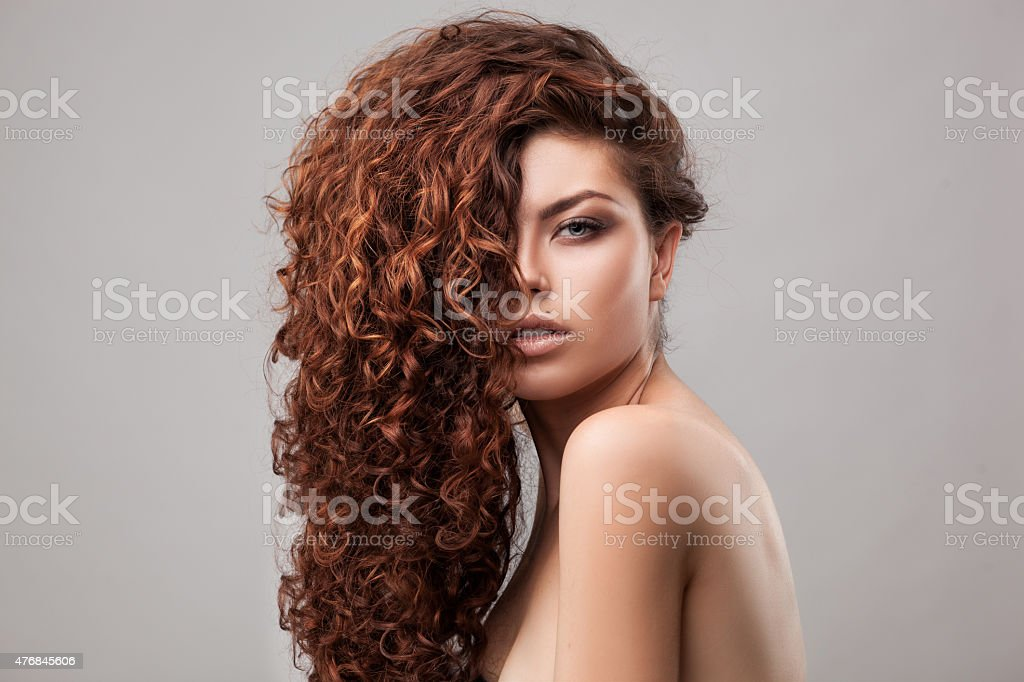 woman with healthy brown curly hair stock photo