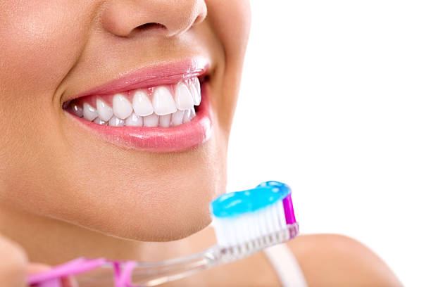 woman with healthy teeth holding a tooth-brush stock photo