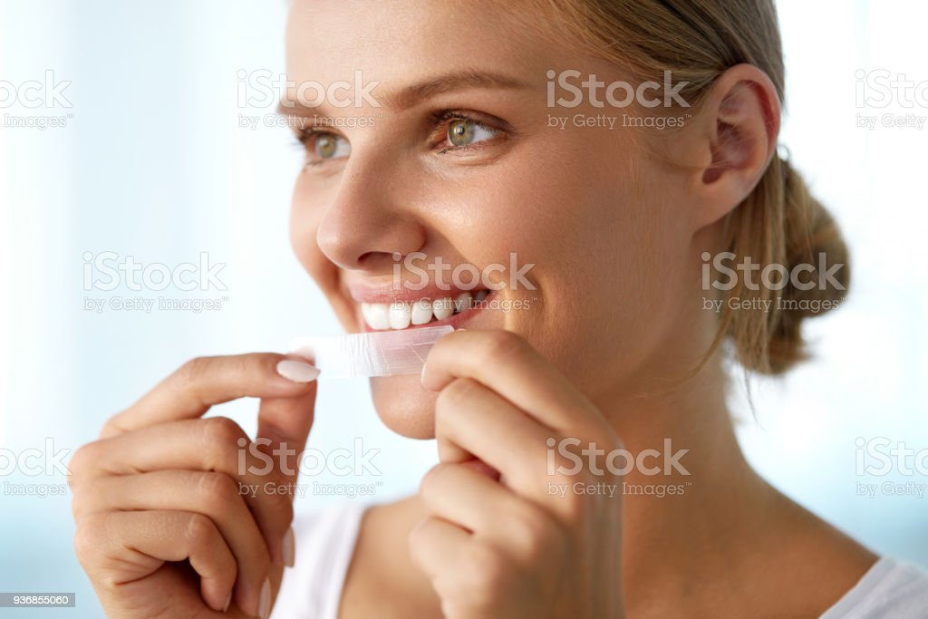 Woman With Healthy White Teeth Using Teeth Whitening Strip Healthy White Teeth. Beautiful Smiling Girl Holding Teeth Whitening Strip. Happy Young Woman With Perfect White Smile Using Dental Whitener. Dental Beauty, Tooth Care Concept. High Resolution Image Adult Stock Photo