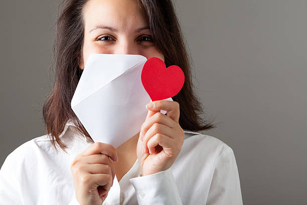 Woman with Heart and Envelop Smiling Woman Holding a Red Heart and an Envelop eastern european descent stock pictures, royalty-free photos & images