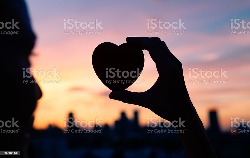 Woman with heart in hand looking at New York skyline at dusk stock photo