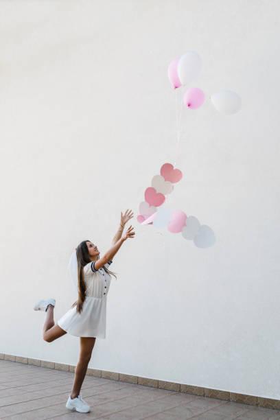 frau mit herzen und rosa luftballons auf bachelorette party im freien. schöne sexy junge mädchen in kleid und schleier auf bachelor-party. jungfernabend, hen-partys. ort für text. - outdoor braut duschen stock-fotos und bilder