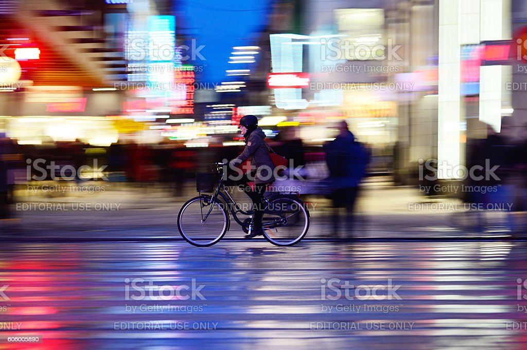 Woman with helmet, biking in night Stockholm stock photo