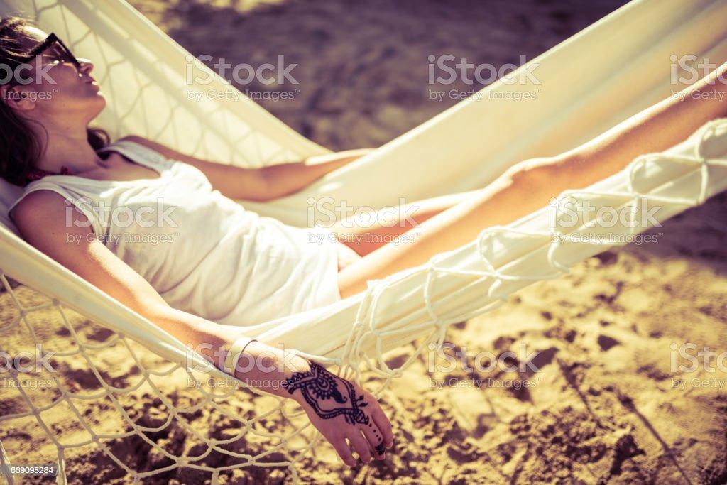 Mulher com tatuagem de henna na mão relaxante numa rede - foto de acervo