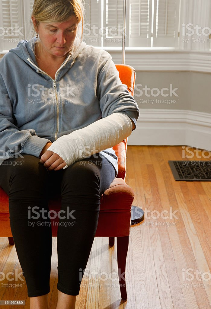 Woman with her arm in a cast at home alone. stock photo