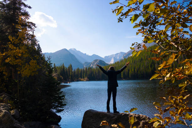 Woman with her arms raised at Bear Lake in Rocky Mountain National Park stock photo