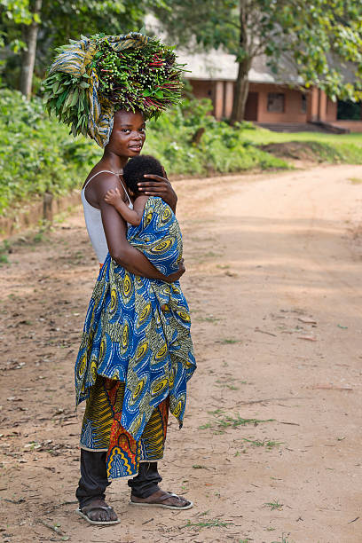 woman with her baby carrying vegetables - democratic republic of the congo stock photos and pictures