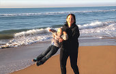 young woman with her 2 year old boy having fun on the beach