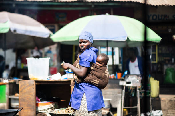 Woman with her child prepares food at a market of Kampala, Uganda. stock photo