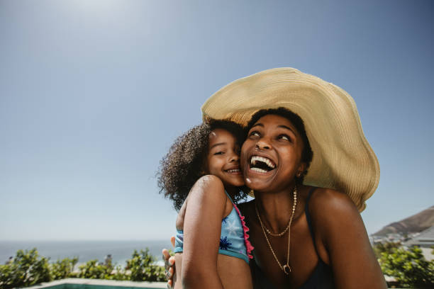 Woman with her daughter having fun at the poolside stock photo