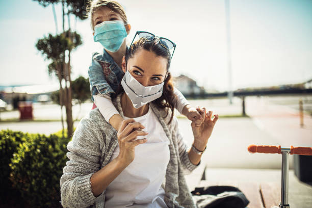 woman with her daughter wearing a protective mask shopping