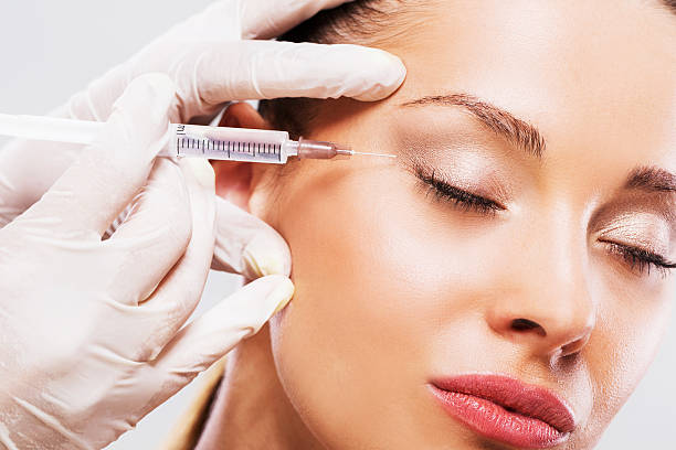 Woman with her eyes closed receiving Botox injection. stock photo