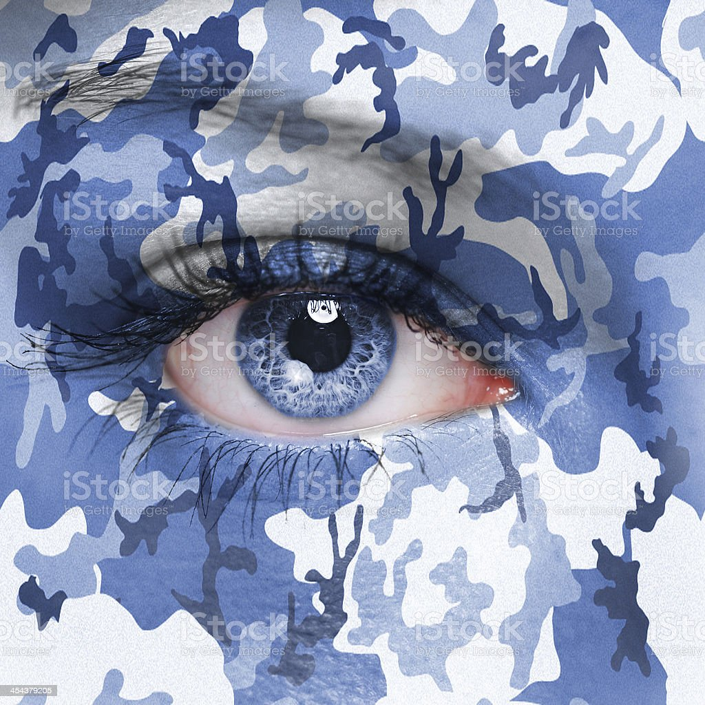 A woman with her face painted in blue camo stock photo