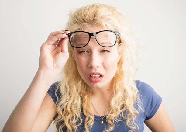 Woman with her glasses lifted up can't see stock photo