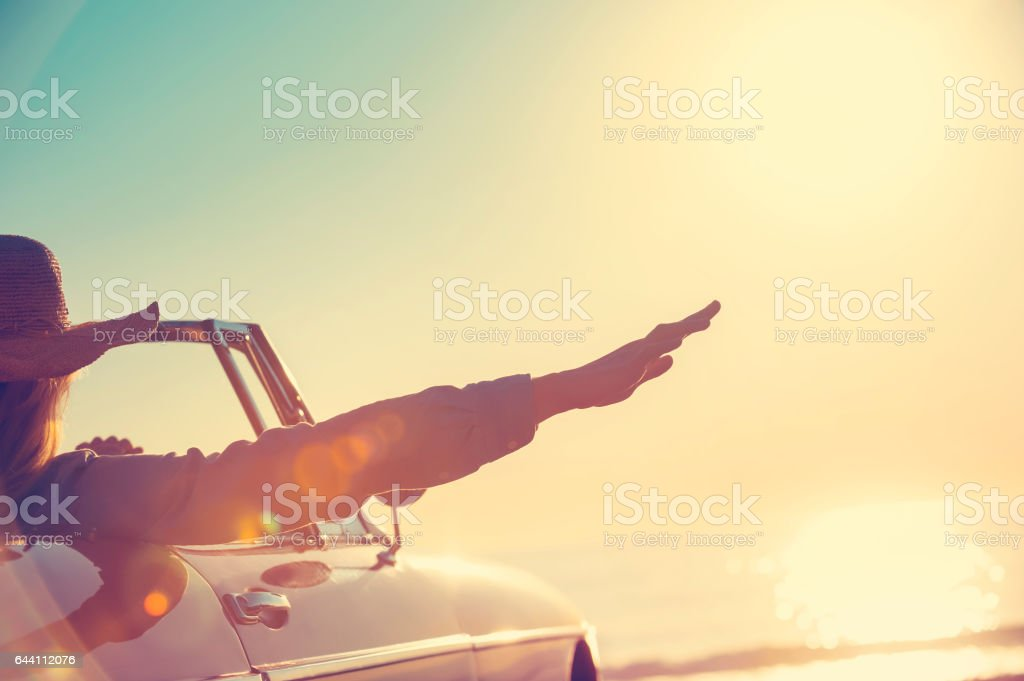 Woman with her hand out of the car window. stock photo
