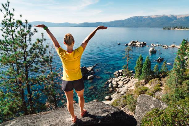 Frau mit ihr Hände in die Luft, am Ufer des Lake Tahoe – Foto