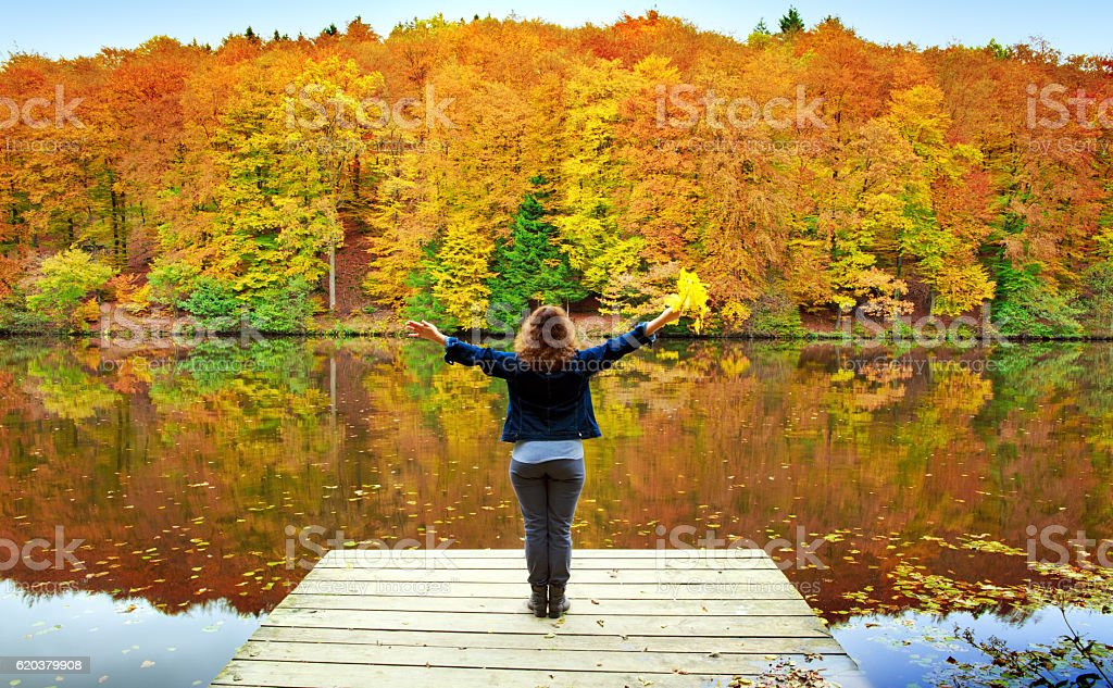 Woman with her hands raised near the beautiful autumn lake. zbiór zdjęć royalty-free