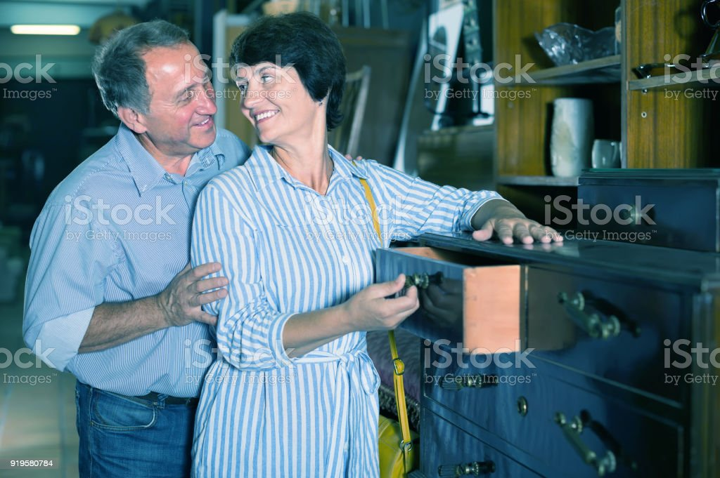 woman with her husband are buying antique curbstone in store stock photo