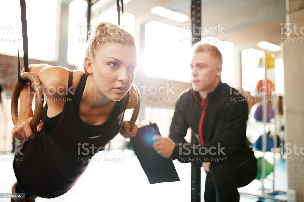 Woman with her personal trainer exercising on gymnastic rings stock photo