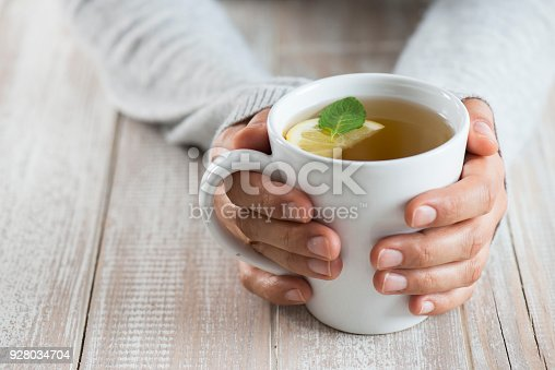 Herbal tea on wood background. Woman holding mug.