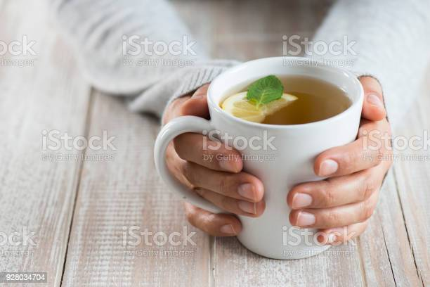 Herbal tea on wood background. Woman holding mug.