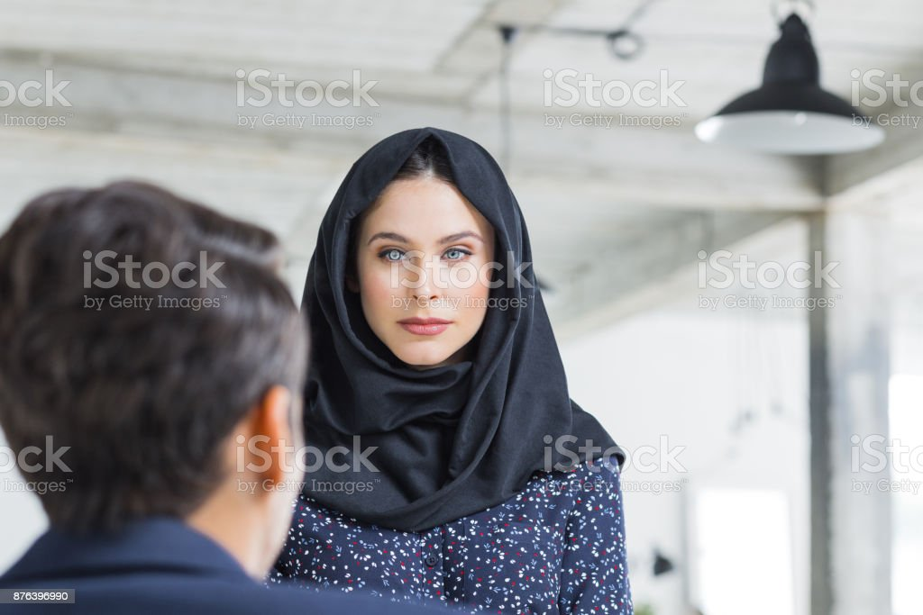 Woman with hijab looking at male colleague Woman with hijab looking at male colleague sitting in front. Businesswoman listening to businessman while working in office. 20-29 Years Stock Photo