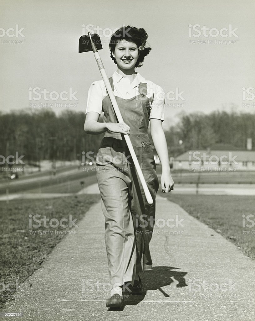 Woman with hoe walking on path, (B&W), portrait royalty-free stock photo