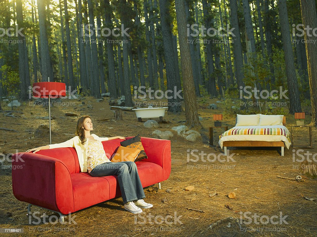 A woman with home furnishings sitting outdoors in the woods stock photo