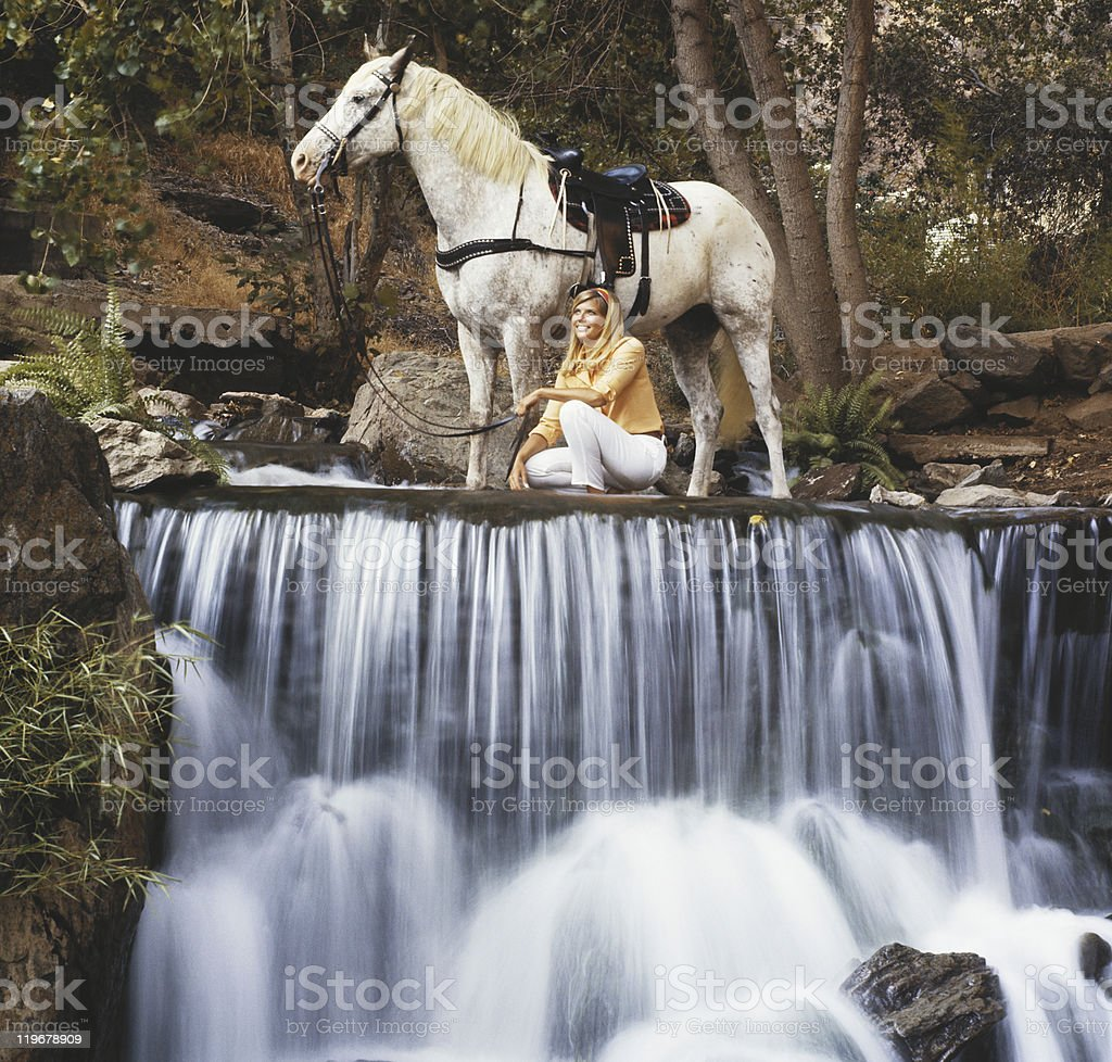 Woman with horse near waterfall stock photo