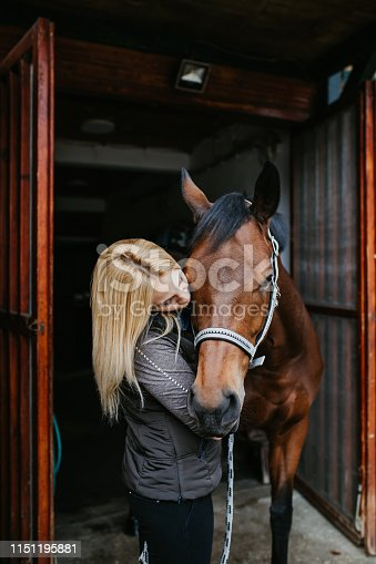 Beautiful young woman enjoying at ranch with her horse.