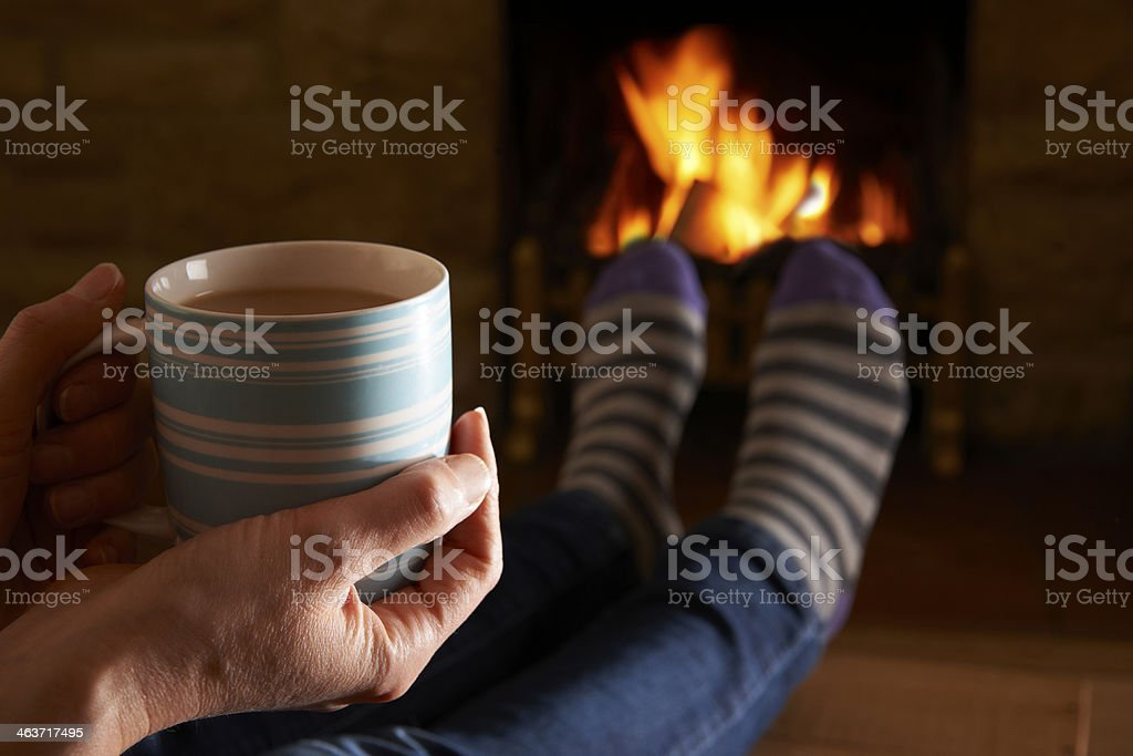 Woman With Hot Drink Relaxing By Fire stock photo
