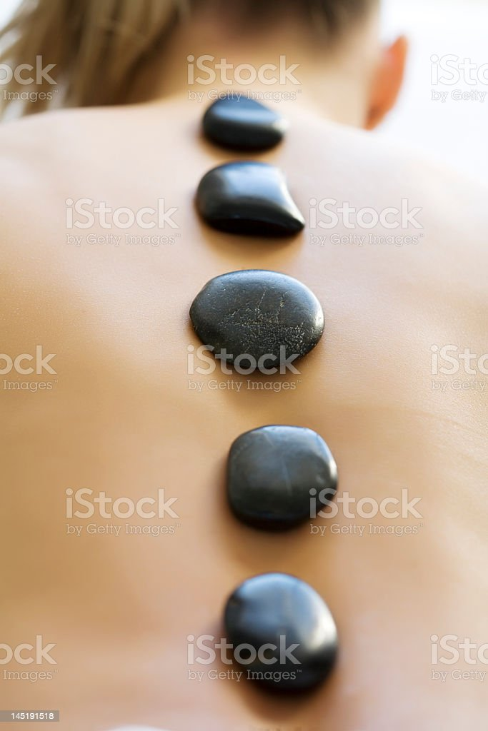 Woman with hot stones on her back at a spa stock photo