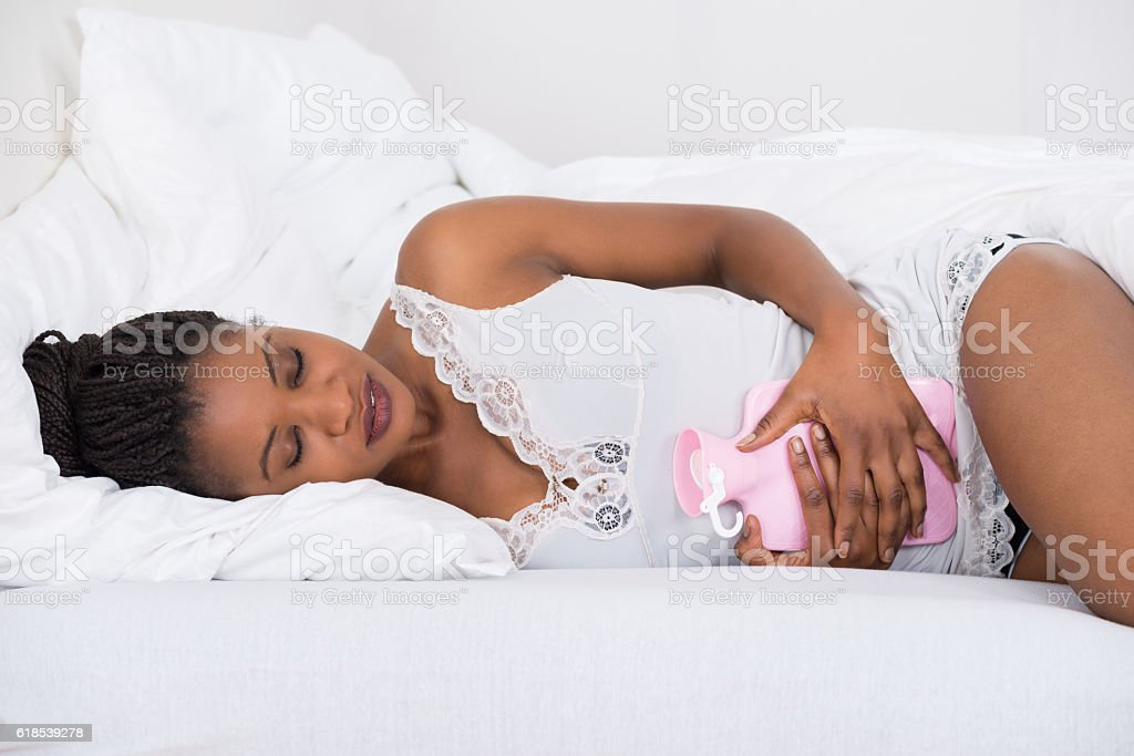 Woman With Hot Water Bag On Bed stock photo