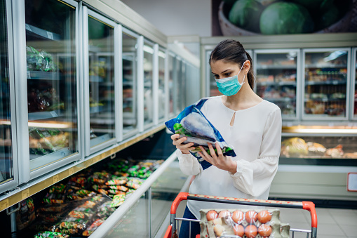 Woman with hygienic mask shopping for supplies.Pandemic quarantine preparation.Choosing nonperishable food essentials from store shelves.Budget buying at a supply store.Food supplies shortage.