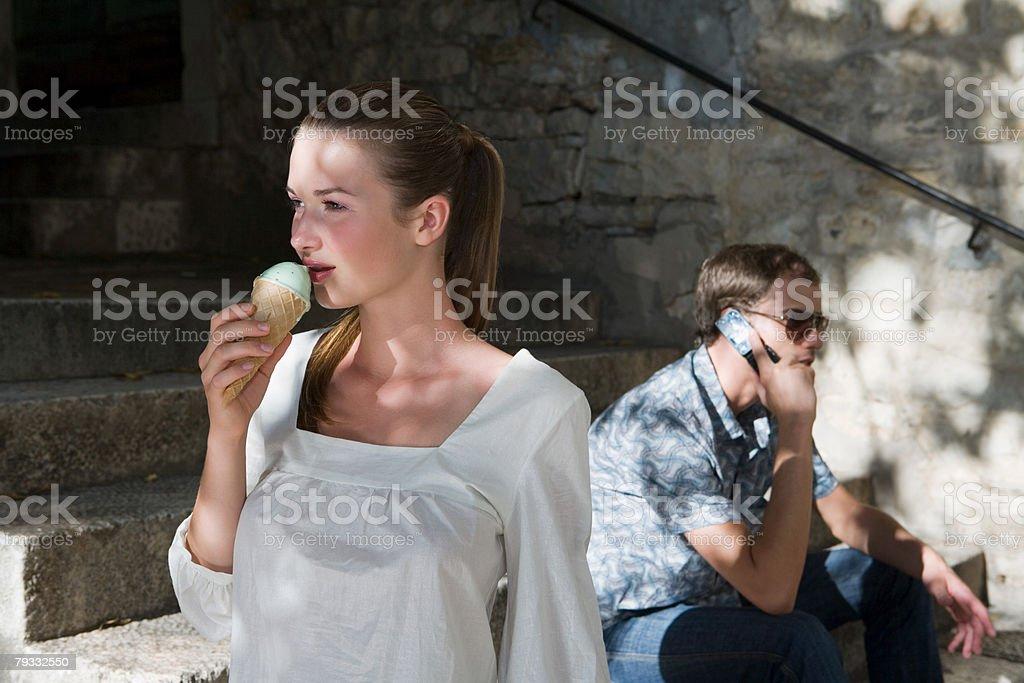 Mulher com gelado e homem com cellphone foto de stock royalty-free