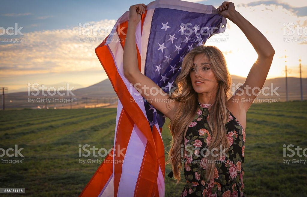 Woman with in field with american flag stock photo