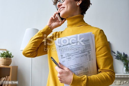 Close-up of positive young woman in glasses standing in living room and holding individual income tax return form while talking by mobile phone