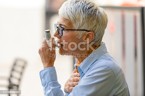 Asthmatic Senior Woman Sitting in the Restaurant and Suffers from Asthma and is Using Inhaler. Senior Business Woman with Grey Hair Suffering from Allergy - Medical Concept.