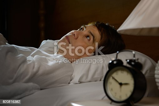 istock Woman with insomnia lying in bed with open eyes 820816382