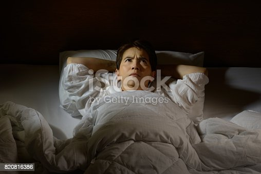 istock Woman with insomnia lying in bed with open eyes 820816386