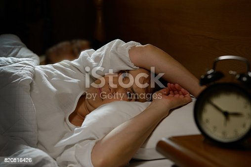 istock Woman with insomnia lying in bed with open eyes 820816426