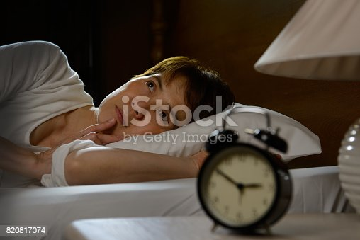 istock Woman with insomnia lying in bed with open eyes 820817074