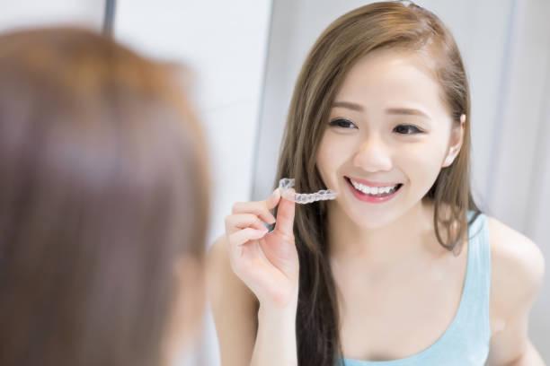 Frau mit unsichtbaren Zahnspangen – Foto
