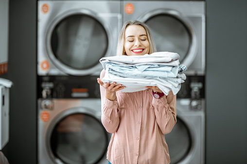 Woman with ironed clothes in the laundry