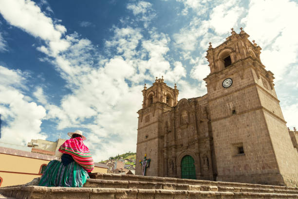Woman with keperina (bag on her back) sitting on the steps of the Cathedral of Puno (Peru) stock photo